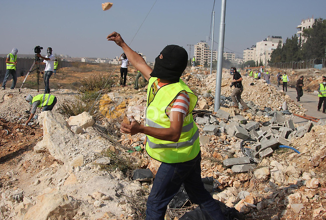 """A Palestinian demonstrators throw stones at Israeli soldiers during a protest in the Qalandia refugee camp, near the West Bank city of Ramallah, on November 9, 2009 to mark the 20th anniversary of the fall of the Berlin Wall in Germany. Palestinians are using the anniversary of the end of the Berlin wall to press their campaign against Israel's """"wall"""", mostly a razor-wire fence interspersed with concrete barricades which Israel began building around the West Bank in 2002. The Jewish state has come under international censure for the barrier's de facto annexation of occupied West Bank land.. Photo by Issam Rimawi"""