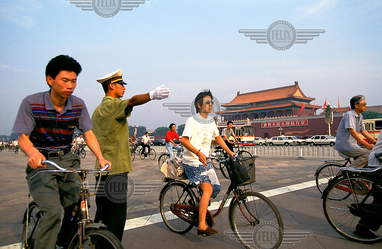 Mark Henley/Panos Pictures..China, Beijing..Policeman controlling traffic on Tiananmen Square.