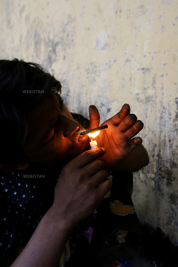 2005. Bangaldesh, Dhaka. A user smokes a joint of heroin. ..2005. Bangaldesh, Dhaka. Un consommateur fume un joint d'héroïne...