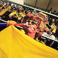A Colombian man plays a vuvuzela while watching the football match between Colombia and Japan at the FIFA World Cup 2014, in a park in Cali, Colombia, 24 June 2014.
