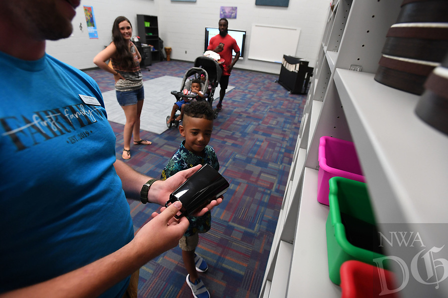 NWA Democrat-Gazette/J.T. WAMPLER  Music teacher Taylor Wilson shows Lihem Mackey, 5, some of the musical instruments that he will be learning Wednesday August 7, 2019 after the ribbon cutting ceremony at Fairview Elementary School, the Rogers School DistrictÕs 16th elementary school.