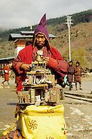 Bhutan, Thimpu.  Mendicant Buddhist monk collecting in the street.