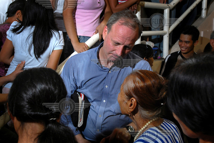 Pastor Steve - an American evangelical preacher - talking with participants after a mass prayer meeting and talent show organised by an international evangelical Christian group.