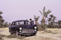 Palmeraie de Marrakech. Un homme avec une voiture devant les palmiers - Marrakech, Maroc - 1973<br /> <br /> on the outskirts of Marrakesh. A Peugeot 404 car with a driver.1973