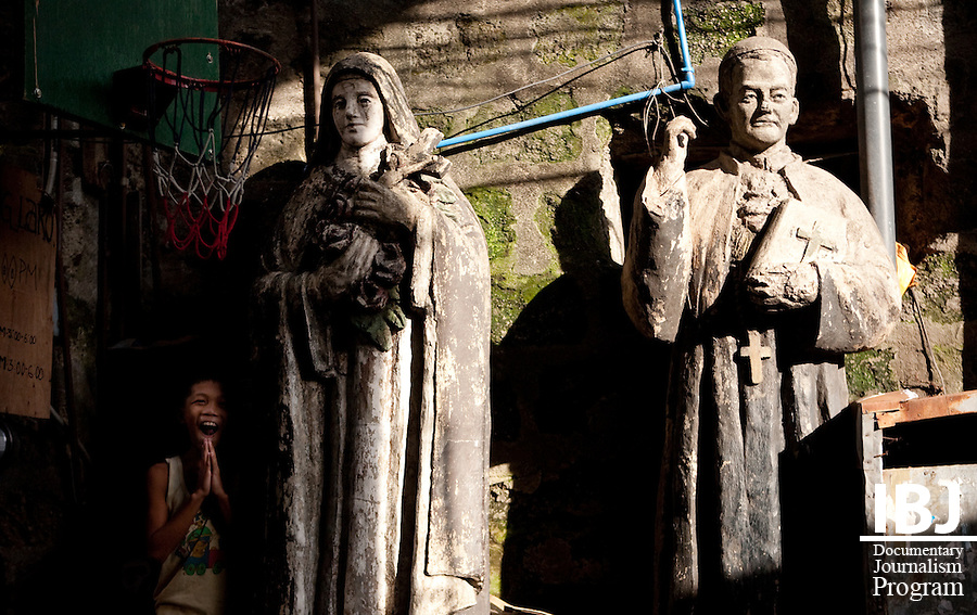Two Catholic statues stand in a residential area of Manila.  The area used to be a park, and when buildings went up, the statues were left standing.