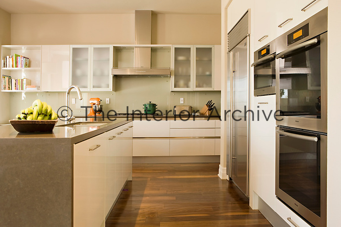 The kitchen is large, contemporary and functional with stainless steel appliances and sleek grey marble worksurfaces