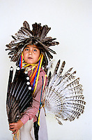 Gallup Navaho India Reservation, New Mexico USA 2005. Boy at Navaho powwow. Children dressed in traditional costumes for the new years pow wow celebration. Their harsh reality is that most who live on the reservations now live below the poverty line. Many hogans have no running water or electricity. Jobs in the vicinity are scarce and alcoholism runs rampant. Vehicles have a difficult time accessing the harsh snow covered plains so many families hunker down in cheap hotels in town for the winter. Still, the Navaho tribes try to cling to some semblance of their culture and instill a sense of identity into their children.