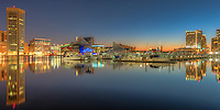 A new day begins in Baltimore with part of the skyline reflected in the still waters of the Patapsco River in the Inner Harbor during the last hour before sunrise.