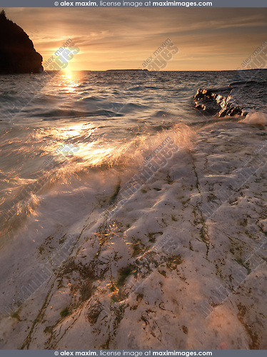 Water hitting against the rocks of Georgian Bay. Sunset landscape nature scenery in golden colors. Bruce Peninsula National Park, Ontario, Canada.