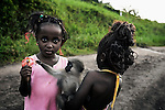 LUKUTU, DEMOCRATIC REPUBLIC OF CONGO MARCH 16: Unidentified girls play with their pet monkey on March 16, 2006 in Lukutu, Congo, DRC. Both girls traveled by boat from Kisangani to Kinshasa, a journey of about 1750 kilometers. About five hundred people traveled on the boat. Congo River is a lifeline for millions of people, who depend on it for transport and trade. During the Mobuto era, big boats ran by the state company ONATRA dominated the traffic on the river. These boats had cabins and restaurants etc. All the boats are now private and are mainly barges that transport goods. The crews sell tickets to passengers who travel in very bad conditions, mixing passengers with animals, goods and only about two toilets for five hundred passengers. The conditions on the boats often resemble conditions in a refugee camp. Congo is planning to hold general elections by July 2006, the first democratic elections in forty years. (Photo by Per-Anders Pettersson)