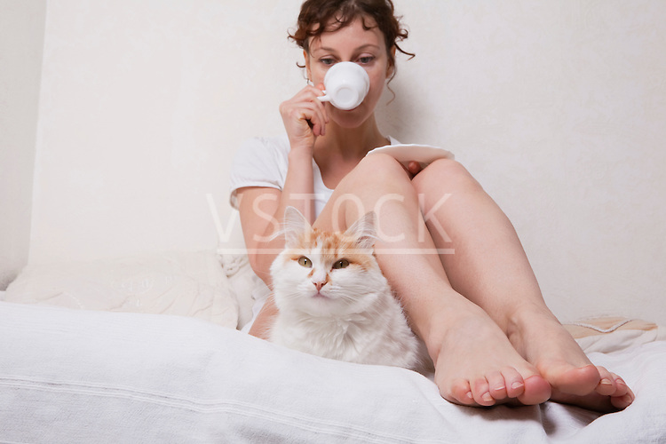 Russia, Voronezh, woman and cat relaxing on bed