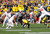 Ohio State Buckeyes linebacker Camren Williams (55) leaps through the air as the Ohio State Buckeyes defense converges on Michigan Wolverines running back Fitzgerald Toussaint (28) in the third quarter of the college football game between the Ohio State Buckeyes and the Michigan Wolverines at Michigan Stadium in Ann Arbor, MI, Saturday afternoon, November 30, 2013. The Ohio State Buckeyes defeated the Michigan Wolverines 42 - 41. (The Columbus Dispatch / Eamon Queeney)