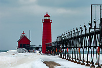 The Grand Haven Pier Tower Light and Pierhead Lighthouse stand darkened and quite for the winter  season, their red colro standing out against a cold February Lake Michigan sky, Grand Haven, Ottawa County, Michigan