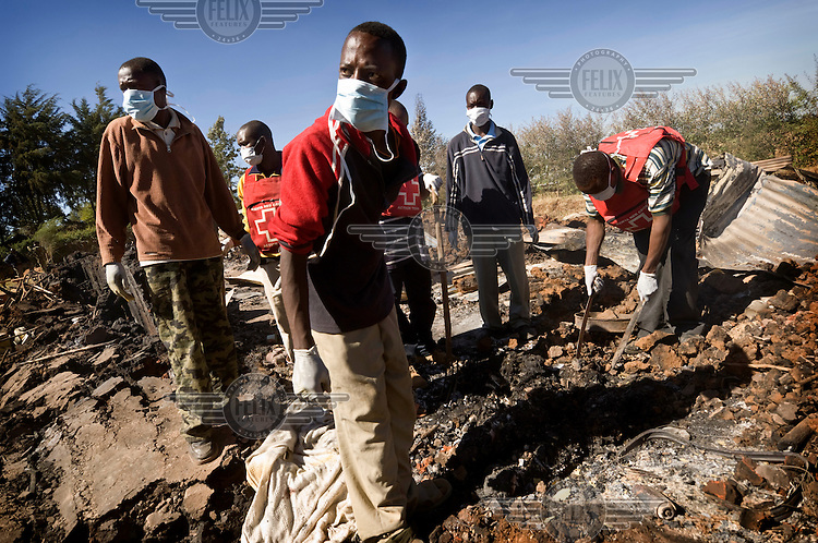 Red Cross workers removing burned bodies from the wreckage of the Kenya Assemblies of God Pentecostal church, a day after it was torched by an angry mob. At least 30 Kikuyu people, many of them children, were killed when members of the Kalenjin tribe attached the church where they had taken refuge. Unrest and ethnic violence followed protests against disputed election results. President Mwai Kibaki, a Kikuyu, was suspected of rigging the vote to retain power.