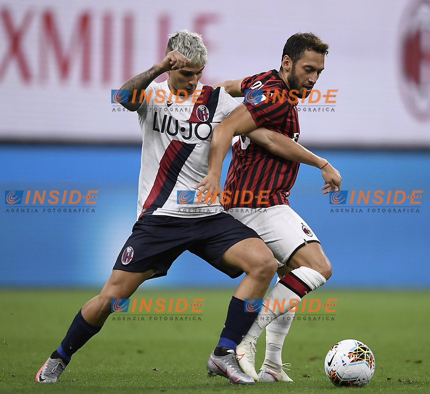 Nicolas Dominguez of Bologna FC and Hakan Calhanoglu of AC Milan compete for the ball during the Serie A football match between AC Milan and Bologna FC at stadio Giuseppe Meazza in Milano ( Italy ), July 18th, 2020. Play resumes behind closed doors following the outbreak of the coronavirus disease. <br /> Photo Image Sport / Insidefoto
