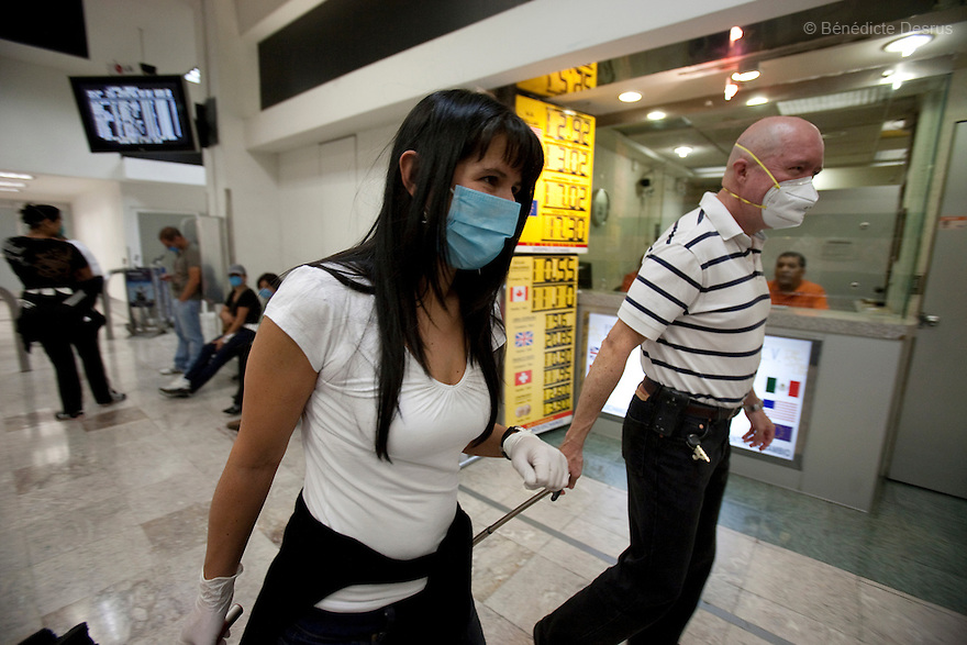 April 26, 2009 - airport, Mexico City, Mexico - A woman arrives in Mexico City prepared for the swine flu with plastic gloves and a surgical mask. Photo credit: Benedicte Desrus / Sipa Press