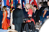 Campaign manager Kellyanne Conway (right in red) embraces President-elect Donald Trump as family and prominent supporters, including New Jersey governor Chris Christie (center) look on after Trump spoke to the crowd in the ballroom in the Midtown Hilton at the election night victory rally for Republican presidential nominee Donald Trump, after the presidential race was called for Trump in the early hours of Nov. 9, 2016.