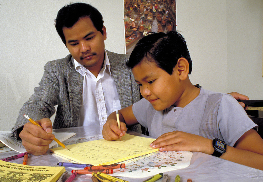CAMBODIAN-AMERICAN FATHER AND SON WORKING ON HOMEWORK. CAMBODIAN-AMERICAN FATHER AND SON. OAKLAND CALIFORNIA.