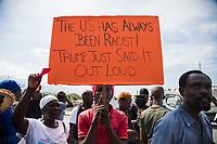 """PTP06. PUERTO PRÍNCIPE (HAITÍ), 18/01/2018.- Centenares de haitianos protestan hoy, jueves 18 de enero de 2018, frente a la embajada estadounidense en Puerto Príncipe (Haití), en rechazo a los supuestos comentarios denigrantes sobre varios países, entre ellos Haití, emitidos la semana pasada por el presidente de Estados Unidos, Donald Trump. En el cartel se lee: """"Estados Unidos siempre ha sido racista ! Trumo solo lo dijo en voz alta"""". EFE/JEAN MARC HERVE ABELARD"""