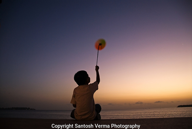 A child holds up a paper windmill towards the sea to catch the sea-breeze that spins his windmill as he looks at it with excitement and thrill. Photograph © Santosh Verma