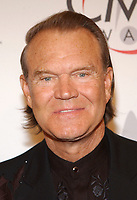 "08 August 2017 - Various - Glen Campbell, the voice behind 21 Top 40 hits including ""Rhinestone Cowboy,"" ""Wichita Lineman"" and ""By the Time I Get to Phoenix,"" died Tuesday. He was 81. During a career that spanned six decades, Campbell sold over 45 million records. In 1968, he outsold the Beatles. Campbell was married four times, and has five sons and three daughters. In the early 1980s, while battling alcoholism and cocaine addiction, Campbell made tabloid headlines with a 15-month, high-profile relationship with country singer Tanya Tucker, who was 22 years his junior. In 1981, he became a born-again Christian and in 1982 he married Kimberly Woollen, a Radio City Music Hall Rockette. In 2003, he was arrested for a hit-and-run, an incident that ended with him allegedly kneeing a police officer in the thigh right before he was released. Campbell pleaded guilty to extreme drunken driving and leaving the scene of an accident, and spent 10 days in jail. In 2011, Campbell, then 75, revealed that he was diagnosed with Alzheimer's disease. In June of that year, he announced he was retiring from music due to the disease. He released his final album of original music Ghost and embarked on a farewell tour with three of his children backing him. File Photo: 15 November 2005 - New York, New York - Glen Campbell. 39th Annual CMA Awards held at Madison Square Garden. Photo Credit: George Shepherd/AdMedia"