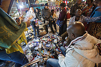 African and Chinese people trade shoes on the street in an area of Guangzhou known to locals as 'Chocolate City', Guangzhou, Guangdong Province, China, 08 December 2014. The health authorities of Guangzhou are said to be stepping up their monitoring of the African community in light of the ongoing outbreak of the Ebola virus disease in West Africa.