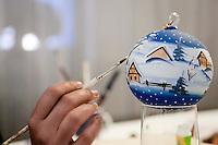 A hand painted glass bauble is given a finishing touch