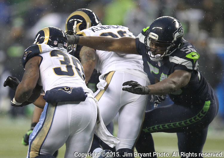 Seattle Seahawks defensive end Cliff Avril (56) reaches for St. Louis Rams running back Todd Gurley (30) at CenturyLink Field in Seattle, Washington on December 27, 2015.  The Rams beat the Seahawks 23-17.      ©2015. Jim Bryant Photo. All Rights Reserved
