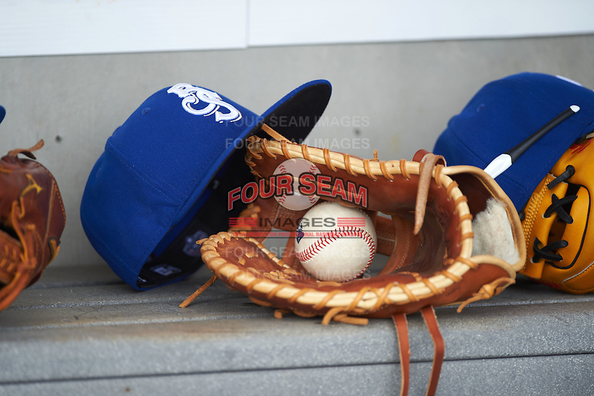 Biloxi Shuckers hat, glove and ball in the dugout before the first game of a double header against the Pensacola Blue Wahoos on April 26, 2015 at Pensacola Bayfront Stadium in Pensacola, Florida.  Biloxi defeated Pensacola 2-1.  (Mike Janes/Four Seam Images)
