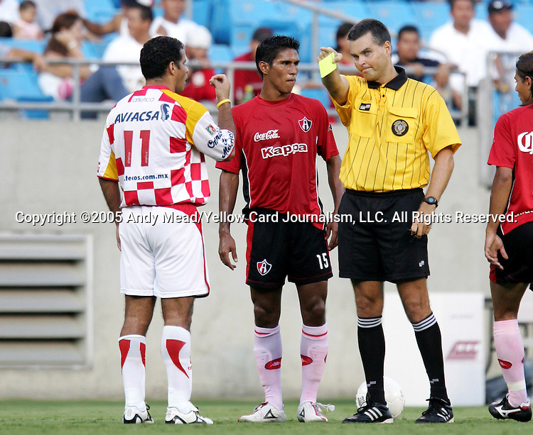 Referee Charles Mitchell (r) issues a yellow card to Carlos Morales (11) of Tecos for delaying a restart by Juan Valenzuela (15) of Atlas on Sunday, July 17, 2005, at Bank of America Stadium in Charlotte, North Carolina. U.A.G. Tecos defeated Atlas (both of the Mexican soccer league) 1-0 in a preseason game.