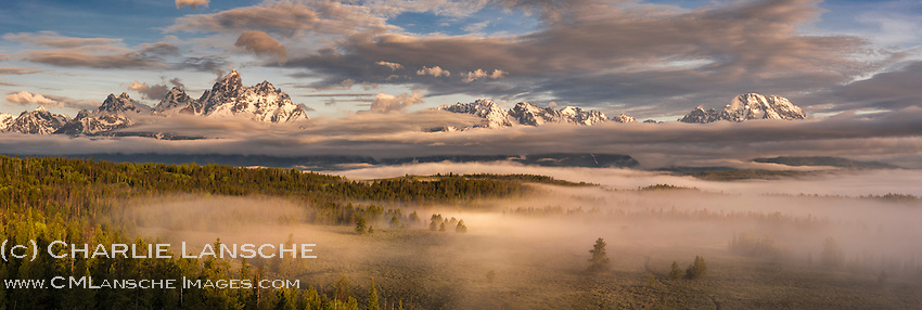 Teton Mist. The Teton Range in Wyoming is a magical place. No matter how many times I visit here, the stunning grandeur of these magnificent peaks robs the breath from my body. On this particular morning, I rolled out of camp at 5 a.m. with hopes of photographing from one of the more classic Teton vistas along the valley floor. When I breathed the chill spring air, it was thick with moisture. I looked to the starless sky and soon realized that fog and clouds had settled into the valley following the previous night's storm, negating any chance of seeing the mountains from lower elevations. So I stayed high on the ridge near my camp, hoping that this vantage point would give me a view of the The Grand Teton and Mt. Moran if and when the fog and clouds lifted. It was so wet before sunrise that I had to continually wipe the moisture from my lens. The minutes ticked, the light brightened, and the clouds and mist began a slow retreat as dawn transitioned into morning. Before long, muted sunlight emerged from the east and the quickly developing scene nearly brought me to tears. It was just so darn beautiful, and big, and wide. And made me feel so small.