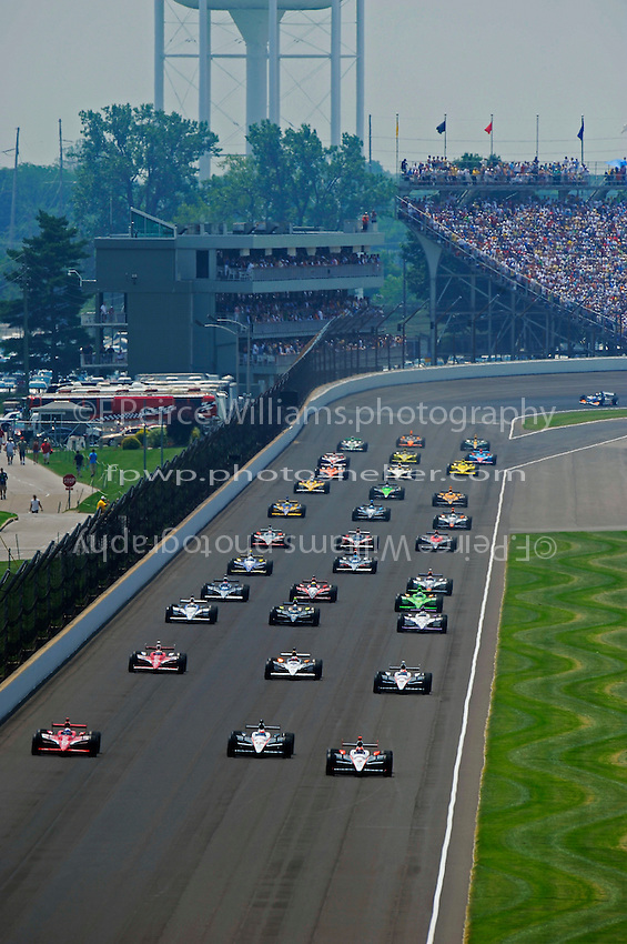 The field lines up along the back straight for the start as the IZOD two-seaterdriven by Michael Andretti and passenger Mark Wahlberg catches the field.