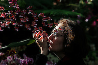 A woman smells orchids during the Orchid show at the botanical garden in Bronx, New York. March 18, 2014. Photo by Eduardo MunozAlvarez/VIEW