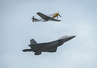 An F-22 Raptor flies in formation with its World War II ancestor, a P-51 Mustang, during a heritage flight at Arctic Thunder 2016 on Joint Base Elmendorf-Richardson. Photo by James R. Evans