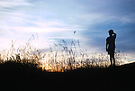 Boy silhouetted at sunset standing on a hill watching a bird take flight