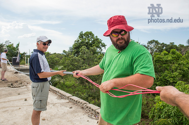Aug. 11, 2015; Ken Oldrid, (right) and Bill Jordan, co-founder of Let's Share the Sun Foundation hook up the wiring for the 26 solar panels on the roof of St. Gabriel School in Fontaine, Haiti. (Photo by Barbara Johnston/University of Notre Dame)
