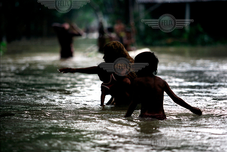 A woman struggles to keep her balance, as she carries her child across the water. Monsoon rains caused flooding in 40 of Bangladesh's 64 districts, displacing up to 30 million people and killing several hundred.