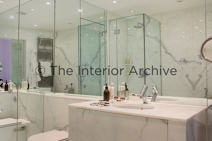 The walls of the master bathroom are lined in carrara marble and mirrors