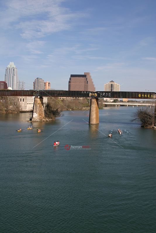 Vertical view of Austinites enjoy canoeing and kyaking under the Union Pacific Railroad Bridge on Lady Bird lake in Austin, Texas.