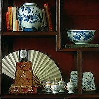 A detail of the Chinese shelves on one wall of the living room displaying a collection of blue and white china and a fan