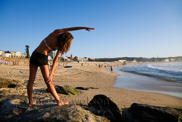 A woman performs morning stretches overlooking Bondi Beach.  Sydney, New South Wales, AUSTRALIA.