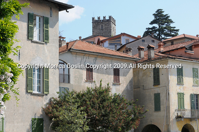 A portrait of the houses, trees, and castle tower in Rezzonico, a town on Lake Como, Italy.