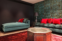 A red and turquoise boudoir that hints at the exotic, with a beaten metal table, plush rug, luxurious seating and a faux tiled wall