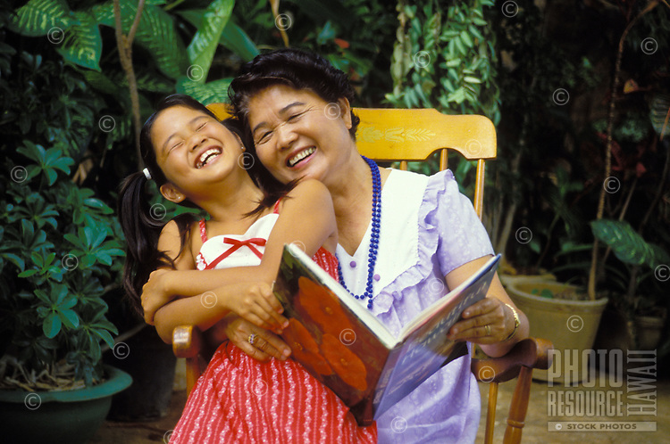 Japanese American grandmother and granddaughter share a light moment while reading a book.