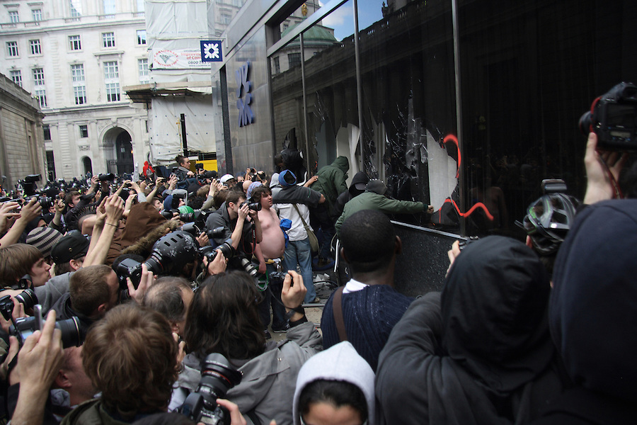 Protesters climb their way into the RBS building after braking the windows at the G20 Demonstration.