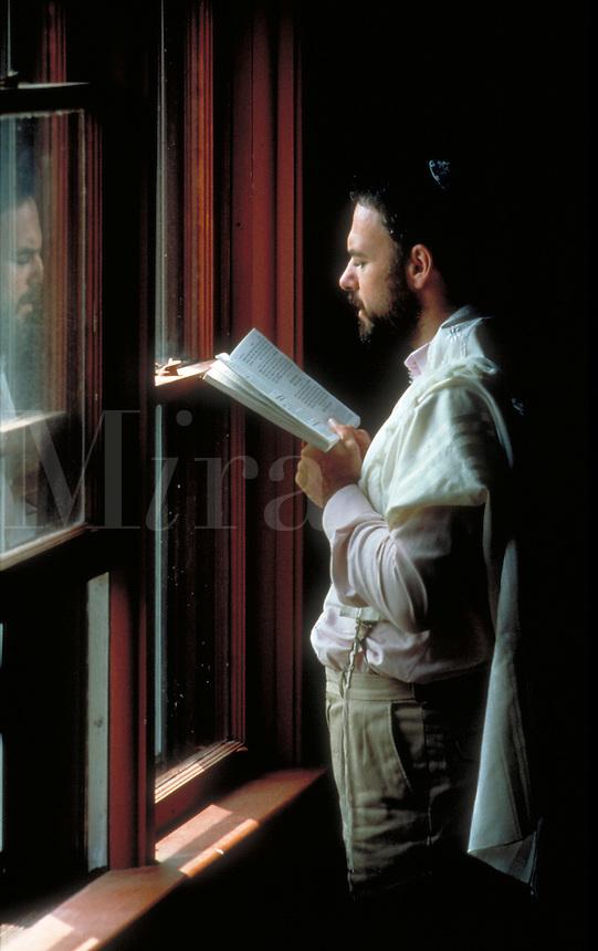 A Jewish man prays alone by a window. Judaism. People. Jewish man.