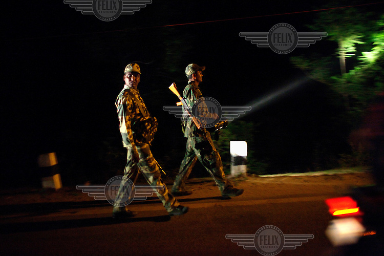 Central Reserve Police Force (CRPF) policemen on night patrol are seen out the window of a moving vehicle in Dantewada. /Felix Features