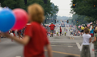 Spectators cross the street as they wait for the Fourth of July parade to move closer to their position.