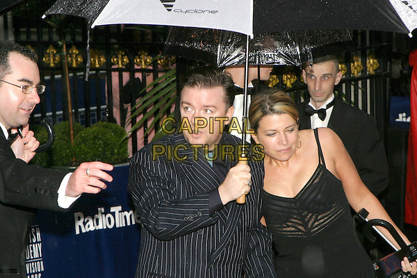 RICKY GERVAIS.The British Academy Televison Awards (BAFTA'S) at the Grosvenor House Hotel, Park Lane, .London,.18th April 2004..half length half-length husband wife umbrella .www.capitalpictures.com.sales@capitalpictures.com.©Capital Pictures