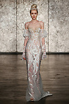 Model walks runway in a spaghetti strap fitted tatto embroidered sheath with removeable puff sleeves, from Inbal Dror Fall 2018 bridal collection on October 5, 2017; during New York Bridal Fashion Week.